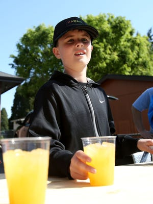 Brennan Parker, 9, sells lemonade Sunday in Keizer during Lemonade Day.