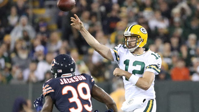 Green Bay Packers quarterback Aaron Rodgers (12) throws on the run over free safety Eddie Jackson (39) Thursday, September 28, 2017 against the Chicago Bears at Lambeau Field in Green Bay, Wis.