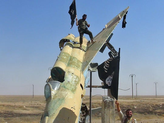 Fighters of the Islamic State wave the group's flag