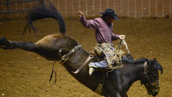 Cody Anthony competes in the Saddle Bronc competition during the SLE Rodeo at Garrett Coliseum in Montgomery, Ala. on Friday March 14, 2014