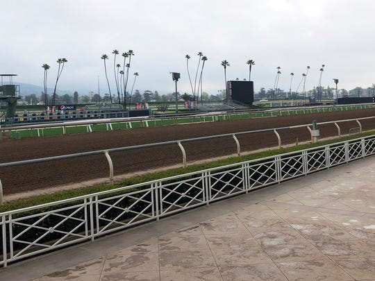 The home stretch and stands are empty at Santa Anita Park in Arcadia, Calif.