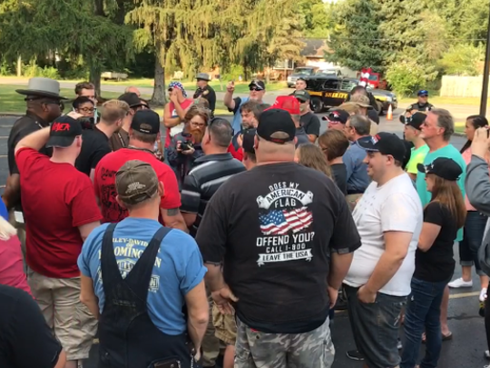 A group of people stand around a socialist activist and debate whether Franklin Township's Confederate monument should be put back or taken down.