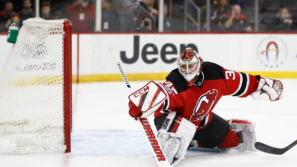 New Jersey Devils goalie Cory Schneider deflects a