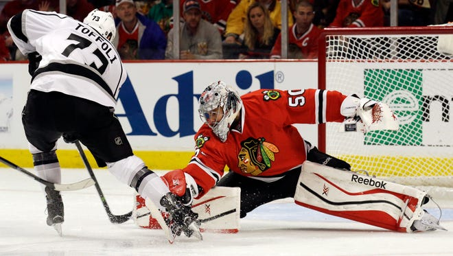 Blackhawks goalie Corey Crawford, right, stops Kings forward Tyler Toffoli during the third period in Chicago on Sunday.
