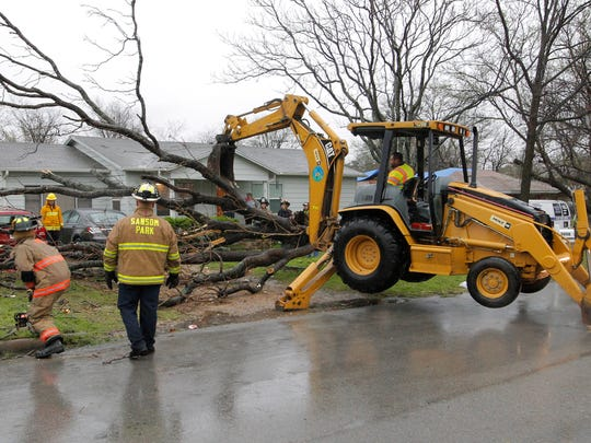 Sansom Park firefighters clear a downed tree that damaged two cars as severe weather crosses the Dallas Fort Worth area, Tuesday, March 8, 2016. Forecasters predict a chance of showers and thunderstorms in the Dallas-Fort Worth area through Thursday.   (Rodger Mallison/Star-Telegram via AP)  MAGS OUT; (FORT WORTH WEEKLY, 360 WEST); INTERNET OUT; MANDATORY CREDIT