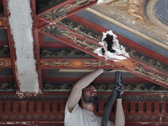 Conservator Greg Steward vacuums away dust and fine plaster powder during an assessment of the decorative ceiling at the Sidney & Berne Davis Art Center in Fort Myers in 2013.