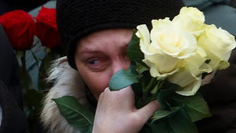 A woman reacts as she lays flowers at Red Square in Moscow.