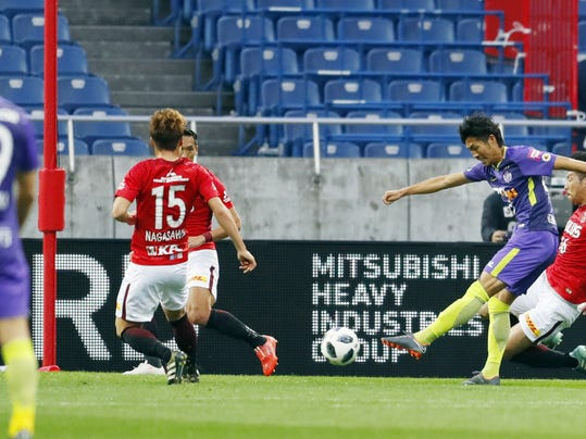 Sanfrecce Hiroshima Kosei Shibasaki, second right, scores a game tying goal during a match against Urawa Reds in Saitama, near Tokyo Sunday, March 4, 2018. Sanfrecce Hiroshima beat Urawa Reds 2-1 away on Sunday in the first round of the J-League's 2018 season. (Yohei Fukai/Kyodo News via AP)