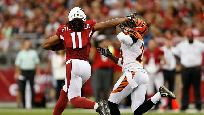 Arizona Cardinals wide receiver Larry Fitzgerald (11) fends off the Cincinnati Bengals cornerback Terence Newman (23) after a reception in the first quarter at the University of Phoenix Stadium. The Enquirer/Jeff Swinger