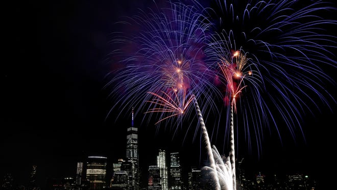 With the New York City skyline in the background, fireworks explode over the Hudson River during the Jersey City Fourth of July fireworks celebration last year. AAA predicts that a record number of people will travel over Independence Day this year.