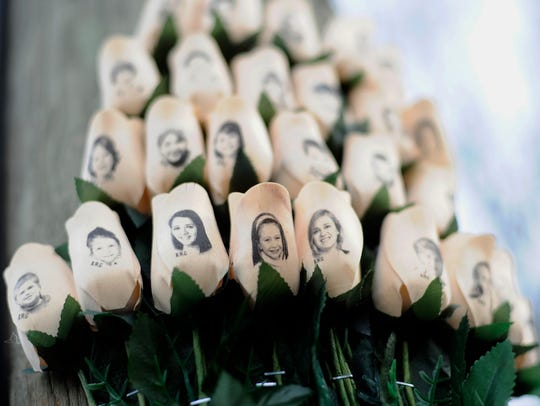 White roses with the faces of victims of the Sandy