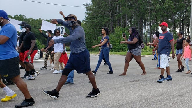 Activists march on Skibo Road to call for racial justice. The city is holding a forum on race Tuesday in an attempt to ease racial tension.