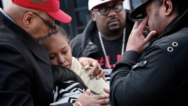 Minister Malik Shabazz, left, hugs Cassie Bass and Talia Bass, the nieces of Janet Wilson who was shot and killed last week.