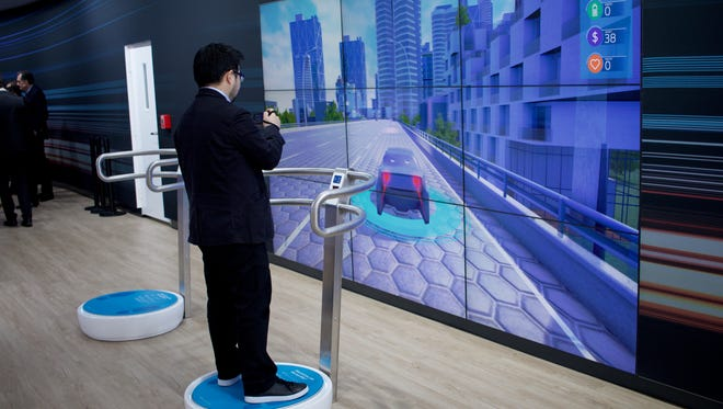 "A member of the press participates in Ford's ""Last Mile"" exhibit inside the North American International Auto Show showroom on Jan. 10, 2016 at Cobo Center in Detroit."
