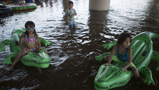 Two young girls play on floaties under a bridge along the Salt River on Saturday, June 24, 2017.