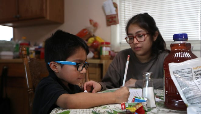 Eric de la Cruz, 8, is tutored by his cousin Yaslin Morales, 16, at the Cruz family home in Quincy on Thursday, Feb. 15, 2018. Cruz is Salvadoran and has lived in the U.S. on temporary protective status for more than ten years, a status that is set to be discontinued by the current administration 2019.