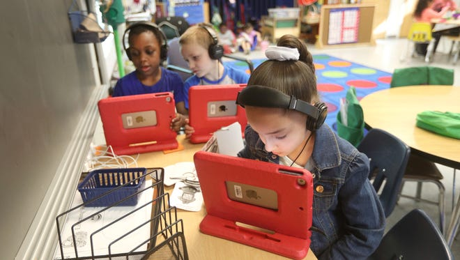Kindergarten students at School 8, Inieris Santiago (front) and Shuaib Hussein (rear left) and Bryan Miller, work on computers during a rotating activity unit.   School 8 and Genesee Community Charter School are collaborating on the K-2 curriculum.