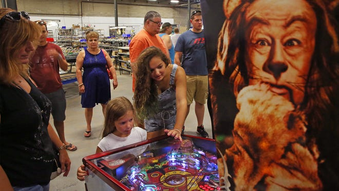 "Zoe Tilis of Matawan helps younger sister Vivienne, 6, try out the ""Wizard of Ozz"" pinball game as their mom Heidi Tilis watches. They were considering buying the game for their home. Pinball manufacturer Jersey Jak Pinball hosted its second annual Jersey Shore Pinball & Gameroom Show. Visitors got to play the games for free andthere was even a section where owners could sell or trade their own old pinball games to other attendees. Jersey Jack showed off their newest game ""The Hobbitt"" in Lakewood on August 29, 2015."