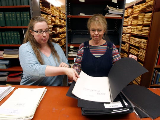 Christina Eaton, associate librarian, left, and Mary Judge, principal librarian, prepare sheet music for a rehearsal of the Cincinnati Symphony Orchestra. They are juggling their regular job while packing up and moving a million pieces of music from the library.