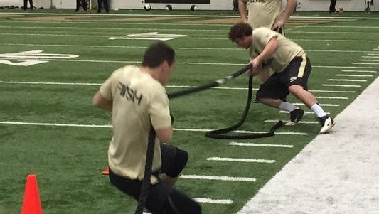 Purdue football players battle in a tug of war competition Monday morning during conditioning drills at the Mollenkopf Athletic Center
