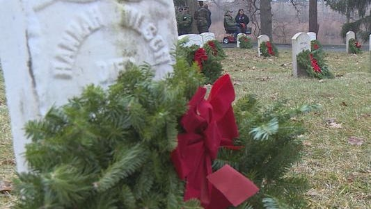 Volunteers lay wreaths upon military graves.