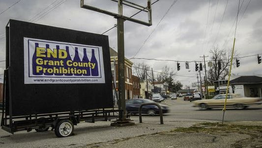 """A car drives past a sign along the main road through Dry Ridge that reads """"END Grant County Prohibition."""""""