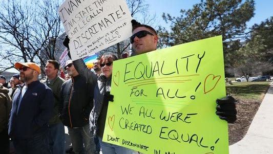 Jeremy Greenwood (right) and Colleen Gannon, both Indianapolis, held signs at the rally on the steps of the Statehouse in Indianapolis where several thousand opponents of Indiana's Religious Freedom Restoration Act (RFRA) held a rally on March 28, 2015.