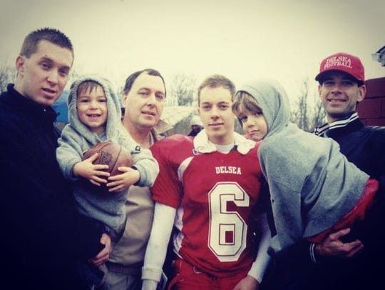 Nick Kargman, second from right, is held by his father Kevin after a Delsea football game in the mid-2000s. Dave Kargman, third from right, was the quarterback of the Crusaders. He's Nick's cousin.