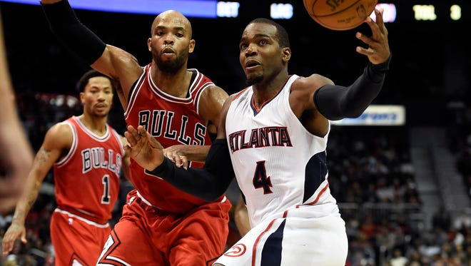 Atlanta Hawks forward Paul Millsap (4) tries to control the ball in front of Chicago Bulls forward Taj Gibson (22) during the second half at Philips Arena.