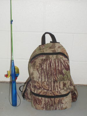 The poacher left this child-size fishing pole and camouflage backpack near the two deal turkeys.