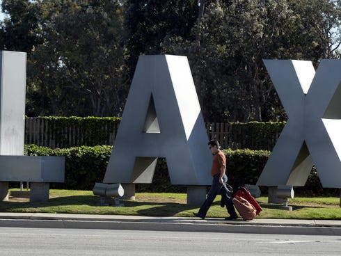 A man passes by the LAX sign.