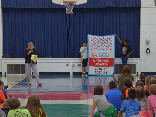 Physical-education teacher Mary Muschinski presents the banner Highland View Elementary was given for receiving the 2017 Active Schools National Award as students unfurl the banner.