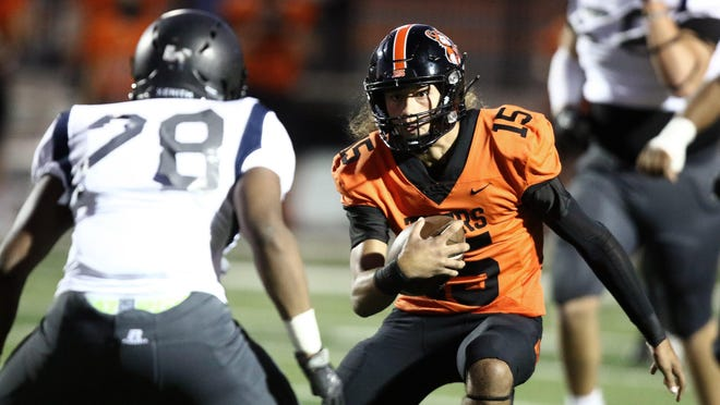 Massillon quarterback Jayvian Crable looks to elude Columbus Bishop Sycamore's Dorian Stevens on this keeper in the first quarter during a game last year.