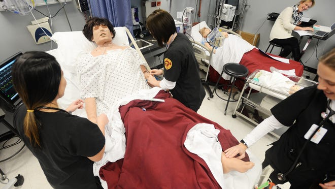 (Left to right) Ana Vale, Sarah Odenbaugh, and Kristi Savat work on a dummy patient in the BPCC nursing lab.