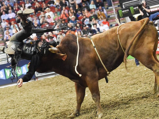 Bull rider Bryan Titman over the head of his bull during the Professional Bull Riders (PBR) Des Moines Invitational at Wells Fargo Arena on Sunday April, 26, 2015.