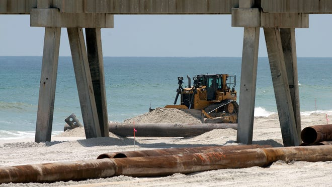 Beach renourishment along Navarre Beach has begun. Work crews are now beginning to move dredging pipes into place and heavy equipment moves sand to create a new shoreline.