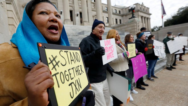 Registered voter Jinnie Brown, of Jackson, joins others as they chant for the electoral college to not cast their electoral votes for President-elect Donald Trump and Vice President-elect Mike Pence in the 2016 General Election at the Capitol in Jackson, Miss., Monday, Dec. 19, 2016.