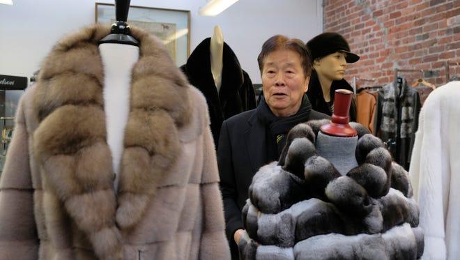 Benjamin Lin poses by fur coats at the B.B. Hawk showroom in San Francisco.