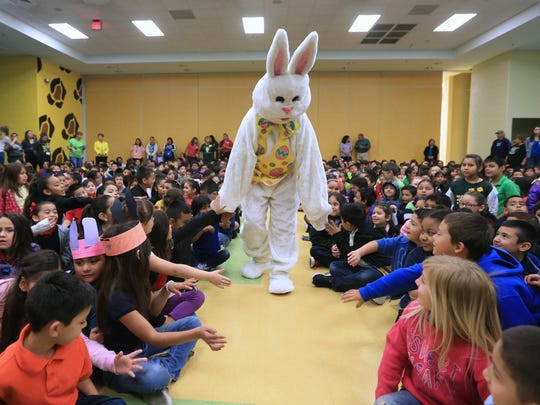 Students at Hicks Elementary School interact with the Easter Bunny as he arrives at the school for the annual Easter event on Thursday, March 24, 2016.