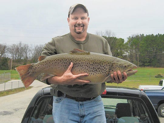 Arnold angler Scott Sandusky hefts the 28-pound, 12-ounce Missouri record brown trout he caught in 2009 at Lake Taneycomo.