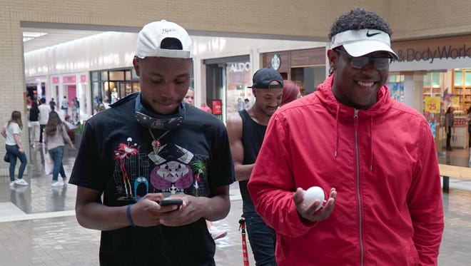Trayvon Washington, 20, plays Pokemon Go while his friend Dre Horton, 19, bounces a Pokemon toy ball in his hand while walking around NorthGate Center mall in Dallas in July, 2016.
