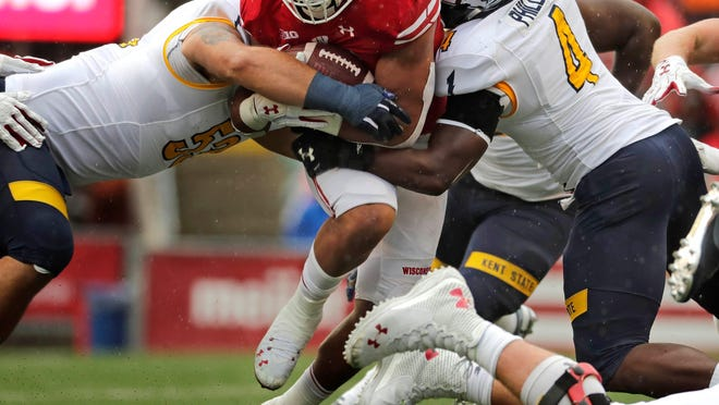 Kent State defenders Alex Hoag, left, and Cepeda Phillips attempt to tackle Wisconsin running back Jonathan Taylor during the teams' matchup in 2019. The Golden Flashes were scheduled to play Penn State in 2020 until the Big Ten canceled all nonconference football games Thursday.