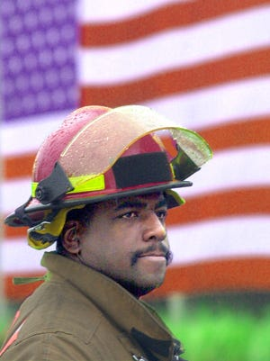 Daryl Gordon stands at Fifth Street and Central Avenue downtown Wednesday morning collecting donations for the families of the New York firefighters lost and injured in the attack on the World Trade Center. Behind him is a huge American flag hung on the outside of WCPO-TV