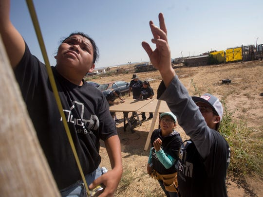 Reheem Trujillo, left, Jezlaine Dan and Tresean Janis work on a house renovation project Thursday in Shiprock.