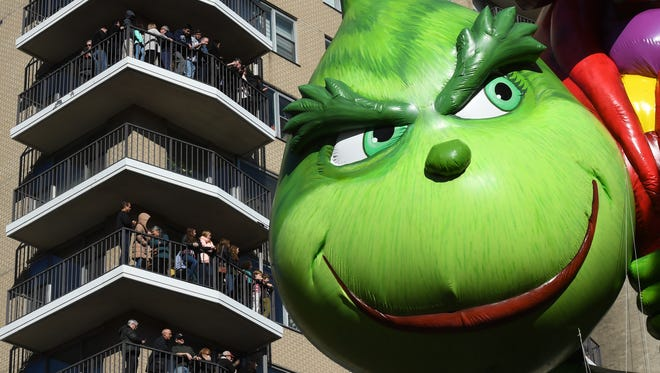 People watch the Grinch Balloon pass by during the annual Macy's Thanksgiving day parade.