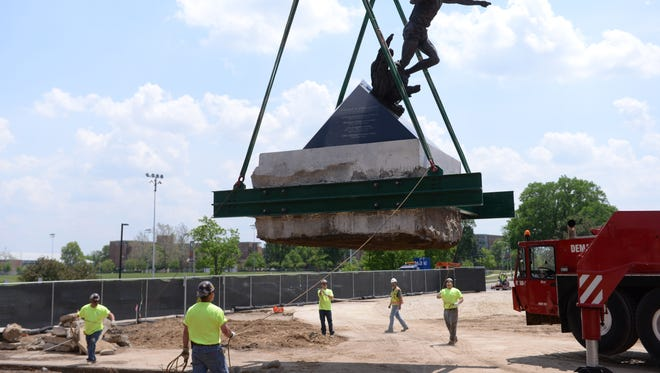 """Workers move the statue of Earvin """"Magic"""" Johnson as part of the ongoing construction project at the Breslin Center on Wednesday, May 25, 2016 in East Lansing. The statue was moved a few yards to the east, which will be a temporary spot for it."""