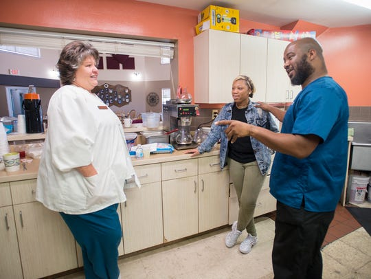 Executive director Deidre Reis, left, chats with kitchen