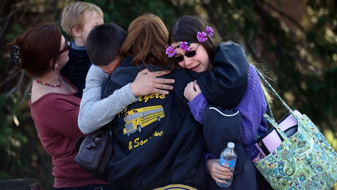 Parents and kids embrace after a knife-wielding suspect stabbed students at Franklin Regional High School in Murrysville, Pa., on April 9, 2014.