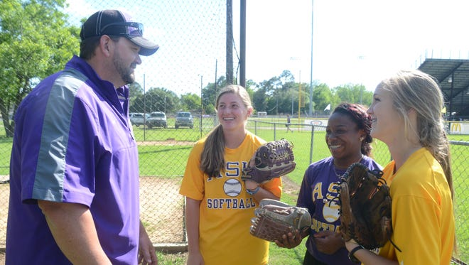 Alexandria Senior High first-year softball Gary Parnham (left) and Lady Trojans Carrie Boswell, Taryn Antoine and Ella Manzer will compete in the Class 5A state softball tournament in Sulphur this weekend.
