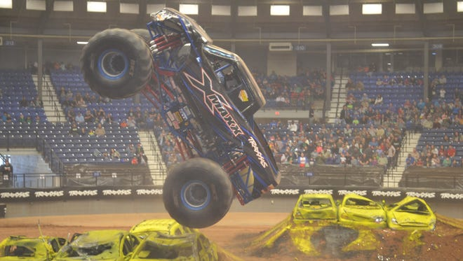 Jeff Murphy drives X-Maxx in a vertical wheelie competition at the Traxxas Monster Truck Show.